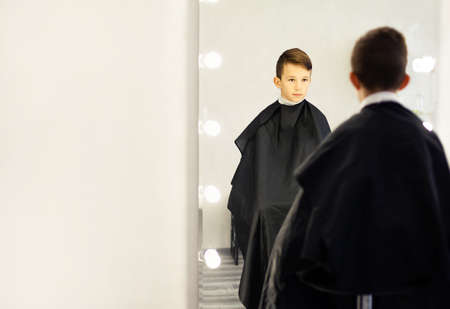 A 10-year-old boy sits in a barbershop chair in front of a mirror. A young child in a beauty salon sits with a black cape, looks in the mirror . Standard-Bild