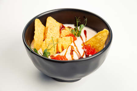 Creamy salmon soup in a black carriage. Ingredients cream, salmon, vegetable oil, salmon caviar, Teriyaki sauce, Nachos chips, salt. For restaurant menu.