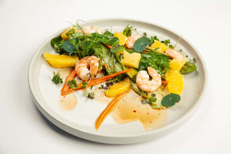 Shrimp salad in soy-ginger dressing on a plate. Ingredients Iceberg lettuce, shrimp, spinach, orange, pineapple, carrot, soy-ginger dressing. For restaurant menu.