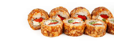 Sushi Roll with fried salmon in Teriyaki sauce on a white plate, ingredients Fried salmon, cream cheese, cucumber, baked pepper, flying fish roe, Spicy sauce, rice, nori. For the restaurant menu