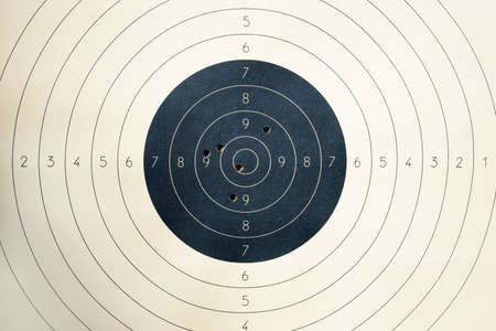 Target with numbers for shooting at a shooting range. A round target with a marked bulls-eye for shooting practice on the shooting range. Target with bullet holes Banco de Imagens