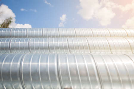 Ventilation pipes against the blue sky. Steel pipes, parts for the construction of air ducts for an industrial air conditioning system in a warehouse. Industrial ventilation equipment.