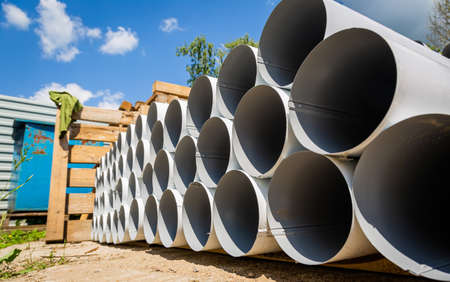 Downpipe warehouse. Steel pipes, parts for the construction of a roof drainage system in a warehouse. Stack of stainless steel pipes. 写真素材
