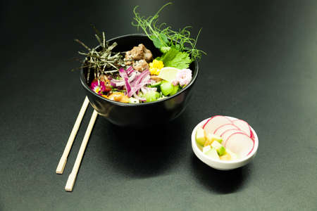 Poke salad with beef in a bowl. Ingredients Beef, Nameko mushrooms, cherry tomatoes, rice, cucumber, red onion, Kim Chi sauce, Ponzu sauce, nori, sesame seeds, cilantro, lime. Asian salad concept. 写真素材