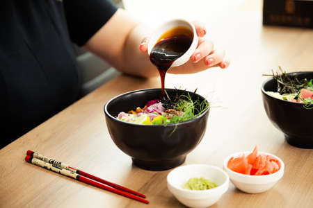 Girl adding teriyaki sauce to Poke salad. Dressing salad with sauce in a restaurant or cafe 写真素材