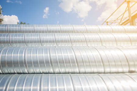 Ventilation pipes against the blue sky. Steel pipes, parts for the construction of air ducts for an industrial air conditioning system in a warehouse. Industrial ventilation equipment