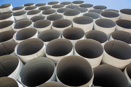Downpipe warehouse. Steel pipes, parts for the construction of a roof drainage system in a warehouse. Stack of stainless steel pipes