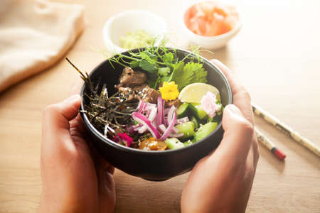 A man holds a Poke salad with beef in a bowl in his hands. Ingredients Beef, Nameko mushrooms, cherry tomatoes, rice, cucumber, red onion, sesame seeds, cilantro, lime. Asian salad concept.