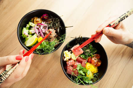 Man and woman eating poke salad with chopsticks. Dab tuna salad in a bowl. People in the restaurant eat salad with chopsticks. Asian seafood salad concept