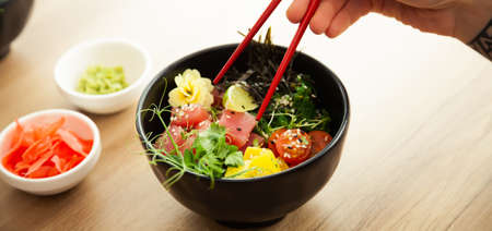 A man eats a Poke salad with tuna in a bowl with chopsticks. Place the tuna salad in a bowl. Young man guy in a restaurant eating poke salad. Asian seafood salad concept