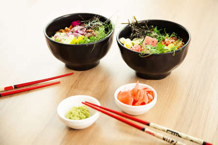 Two poke salads with beef and tuna in a bowl on a restaurant table. Poke salads in a bowl next to chopsticks and ginger with wasabi. Asian salad concept.