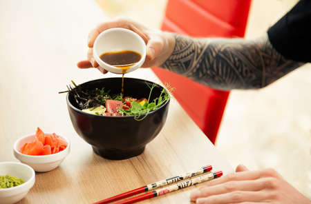 A man adds soy sauce to Poke salad. A man's hand pours soy sauce into a bowl of salad. Guy young man dressing salad with sauce in a restaurant or cafe. 写真素材