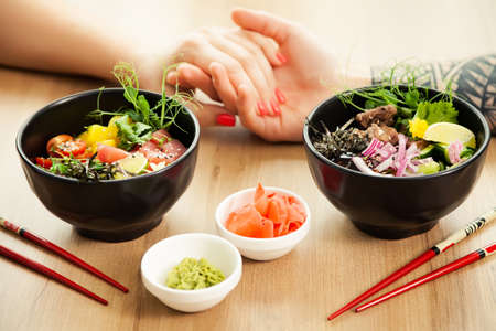 Loving couple man and woman eating salad poke chopsticks. Place the tuna salad in a bowl. People in the restaurant eat salad with chopsticks. Asian seafood salad concept