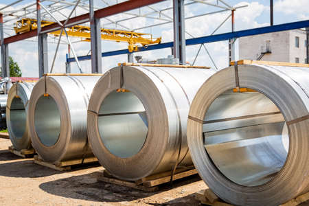 Stainless steel rolls. Rolls of steel sheet in the warehouse. A roll of galvanized steel sheet for the production of metal pipes and tubes in a factory