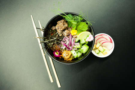 Poke salad with beef in a bowl. Ingredients Beef, Nameko mushrooms, cherry tomatoes, rice, cucumber, red onion, Kim Chi sauce, Ponzu sauce, nori, sesame seeds, cilantro, lime. Asian salad concept
