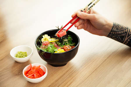 A man eats a Poke salad with tuna in a bowl with chopsticks. Place the tuna salad in a bowl. Young man guy in a restaurant eating poke salad. Asian seafood salad concept. 写真素材