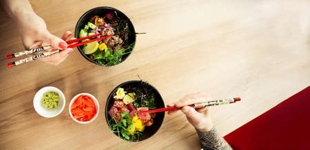 Loving couple man and woman eating salad poke chopsticks. Place the tuna salad in a bowl. People in the restaurant eat salad with chopsticks. Asian seafood salad concept.