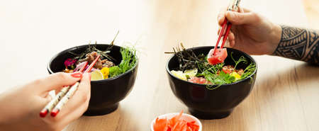 Man and woman eating poke salad with chopsticks. Dab tuna salad in a bowl. People in the restaurant eat salad with chopsticks. Asian seafood salad concept.