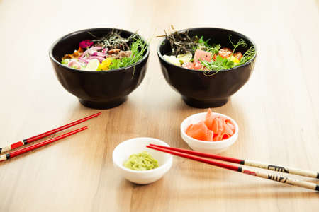 Two poke salads with beef and tuna in a bowl with various sauces on the restaurant table. Poke salads in a bowl next to chopsticks and ginger with wasabi. Asian salad concept