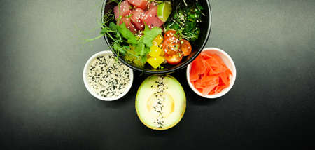 Poke salad with tuna in a bowl. Ingredients fresh tuna, cherry tomatoes, marinated seaweed, rice, takuan, Ponzu sauce, Teriyaki sauce, nori, sesame seeds, lime, cilantro. Asian seafood salad concept.