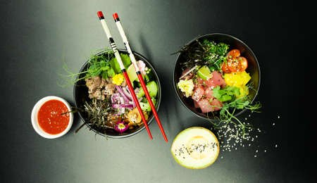 Poke salads with tuna and beef in bowls on the table. Two bowls of poke salad with chopsticks on a gray background. Asian seafood salad concept 写真素材