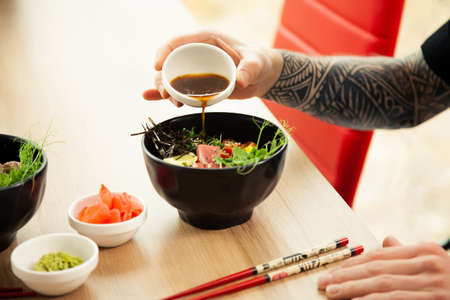 A man adds soy sauce to Poke salad. A mans hand pours soy sauce into a bowl of salad. Guy young man dressing salad with sauce in a restaurant or cafe 写真素材
