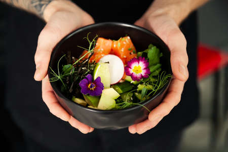 A hand holding a bowl of salad