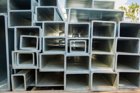 Ventilation pipes are square and rectangular. Steel pipes, parts for the construction of air ducts for an industrial air conditioning system in a warehouse. Industrial ventilation equipment.