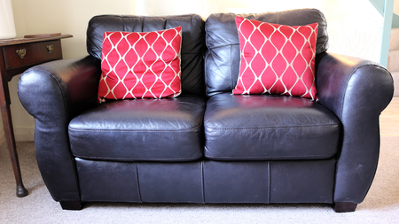 Black Leather Sofa with Red Cushions Stock Photo