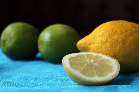 One Whole Lemon with a Sliced Lemon in front of Whole Limes on a Blue Background