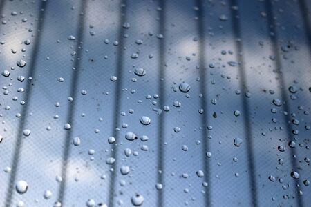 Raindrops on a glass door with mesh curtain Stockfoto