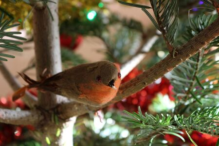 A red robin decoration hanging on a Christmas tree