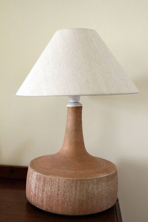 A close up of a wooden lamp on the corner of a table in a room