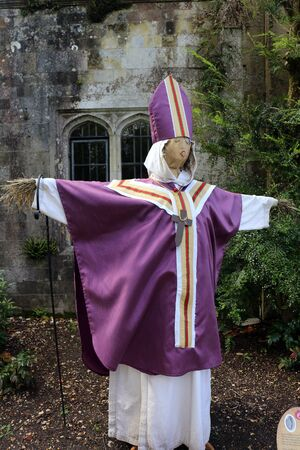 A scarecrow figure in a purple and white chasuble