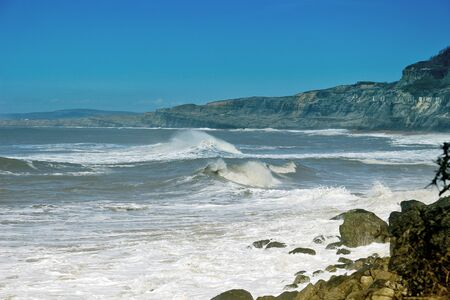 Waves crashing off the coast with cliffs in the distant