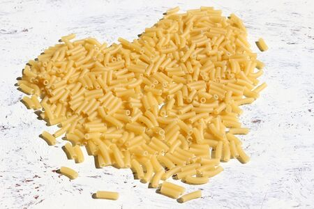 Dry Pasta Background. Uncooked macaroni pasta in the shape of a heart on a white background Stockfoto
