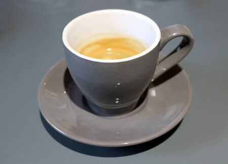 A demitasse cup with a single shot of espresso coffee in