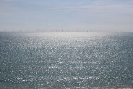 Sparkling sea with wind turbines on the horizon