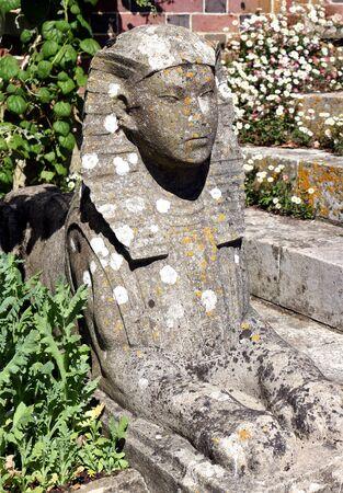 A stone sphinx statue in a garden in England