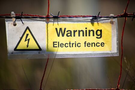 An electric fence warning sign Фото со стока