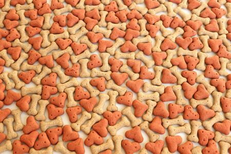 Bone and heart shaped dog biscuits. Dog treat background.