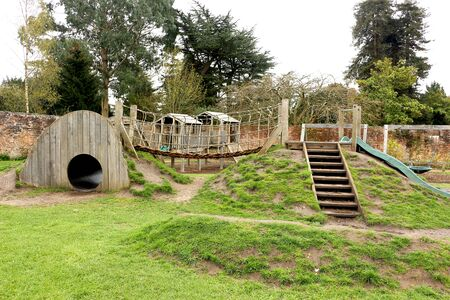 A childrens playground constructed using natural materials including wood and rope. A tunnel and slide built into the earth are connected by a climbing bridge. Stockfoto