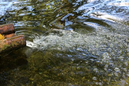 Water flowing from a spout into a clear stream