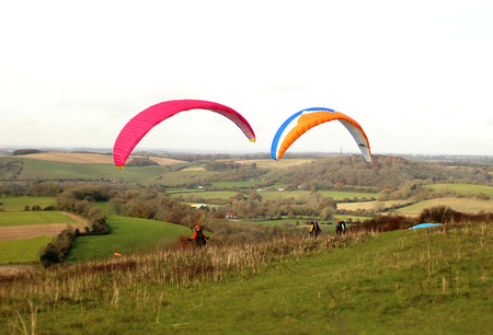 Butser Hill, Hampshire, England. 13th November 2019. Paragliders preparing to take off over the South Downs National Park.