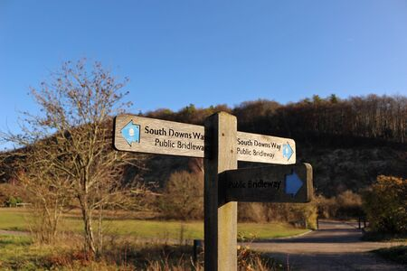 A signpost between Butser Hill and Queen Elizabeth Country Park in Hampshire pointing to the South Downs Way, a long distance footpath and bridleway running along the South Downs in southern England.