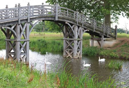 A wooden bridge in the countryside with three swans swimming underneath. Фото со стока