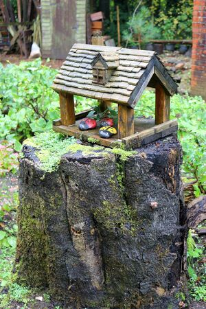 A wooden birdhouse on top of a tree trunk with pebbles painted as ladybirds