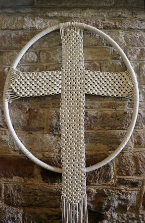 A macrame cross hanging on a wall
