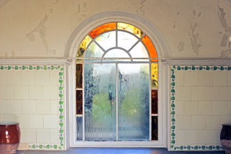 A small arched window with a tile surround Фото со стока