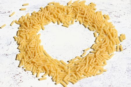 Dry Macaroni pasta in the shape of a heart on a white surface